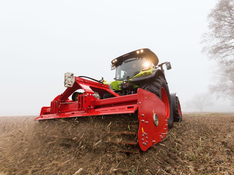 Traktor mit Mulcher im Acker beim Mais häckseln